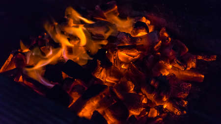 Red coals of a fire burning at night time.