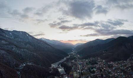 Luftaufnahme von Krasnaya Polyana bei Sonnenuntergang, schneebedeckte Berge.