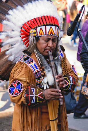 american music: Portrait of a native american playing at a flute