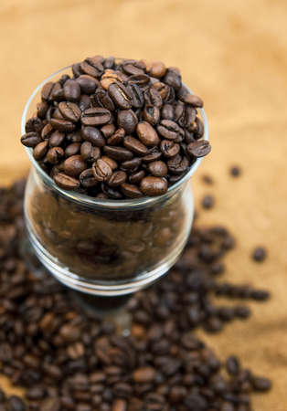 Grains of black roasted coffee in transparent cup Stock Photo