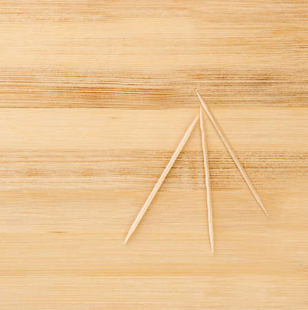 three toothpicks on a light wooden table Stock Photo - 13779553
