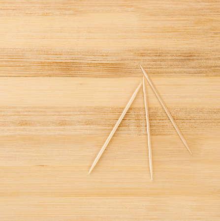 three toothpicks on a light wooden table Stock Photo - 13779553