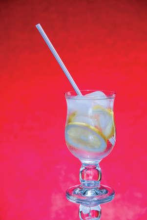 koude verse limonade met ijs op rode achtergrond Stockfoto