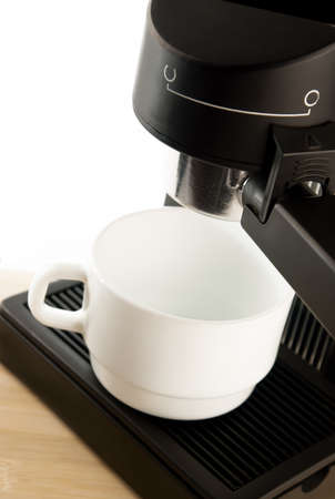Close up coffee maker machine with white coffee cup photo