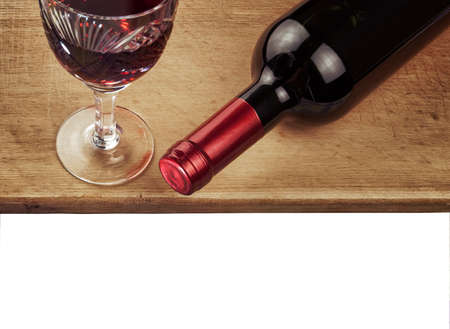 bottle of red wine and glass of wine against a wooden table on white background photo