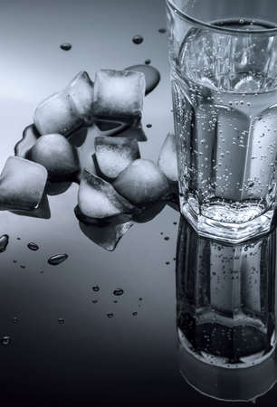 glass of water and ice cubes on a dark background of the mirror Stock Photo - 14123050