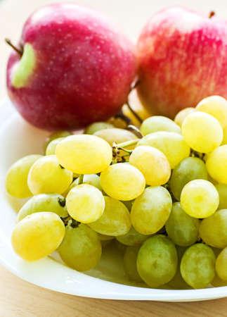 Apple and grape fruit on dish, on white background Stock Photo - 14983774