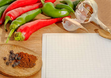 hot chili peppers, garlic and spices  border and blank paper for recipes Stock Photo - 16650086