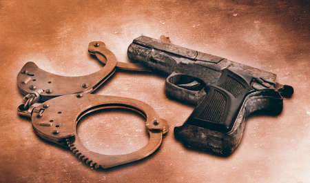 Gun and handcuffs on table  Photo in old color image style photo