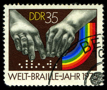 DDR- CIRCA 1975: A stamp printed in DDR, shows  hands reading a font of Braille , circa 1975 Stock Photo - 21417560
