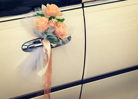Door of white wedding car with flowers and white bow photo