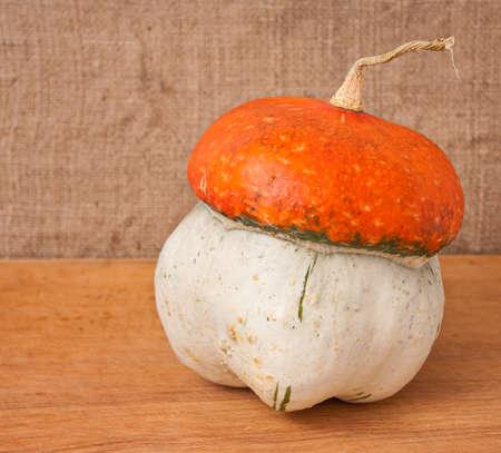 decorative pumpkin (Cucurbita pepo) on a wooden table