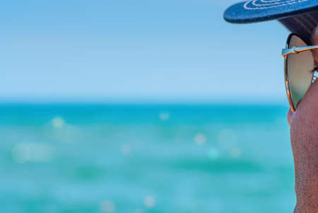 Güneş gözlüğü tıraşsız adam denize bakarak, denizin sığ alan derinliği