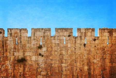 Defensive wall of the ancient holy Jerusalem, lit by the bright sun. Photo in old color image style.