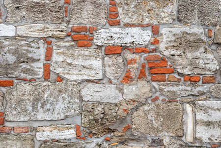 suitability: Broken old bricklaying wall fragment from red white bricks and damaged plaster background texture.