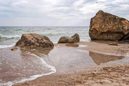 Stones at the seashore in cloudy weather Stock Photo