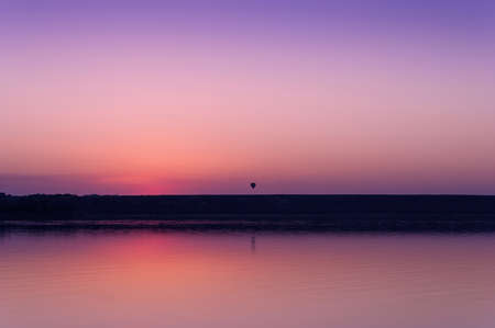 Colorful bright orange red summer sunset over lake and a balloon on a background