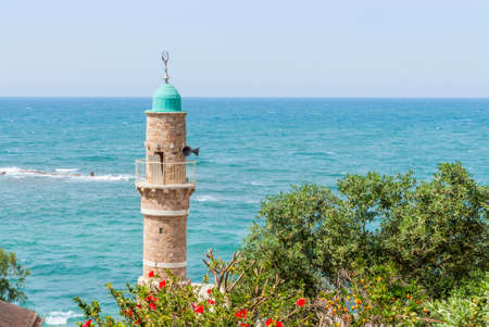 holyland: Minaret of the mosque in old Jaffa on blue sky and Mediterranean sea background. Israel. Stock Photo