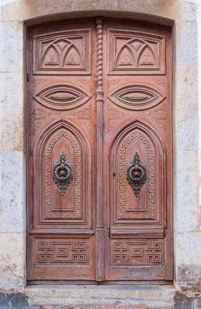 Old wooden decorative door in medieval Old Town - Vila Vella Spain, Tossa de Mar.