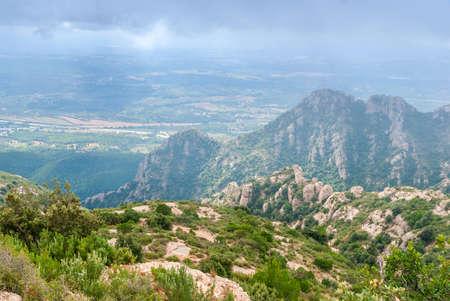 Hazy unusual mountains with green trees and cloudy sky near Montserrat Monastery,Spain. Catalonia