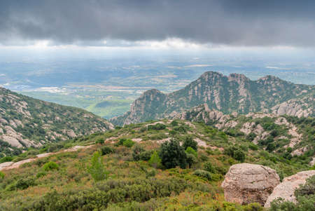 Hazy unusual mountains with green trees and cloudy sky near Montserrat Monastery,Spain