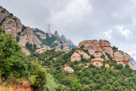 Hazy unusual mountains with green trees and cloudy sky near Montserrat Monastery,Spain Stockfoto - 121868531
