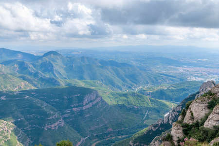 Hazy unusual mountains with green trees and cloudy sky near Montserrat Monastery,Spain. Catalonia Stockfoto - 121868556