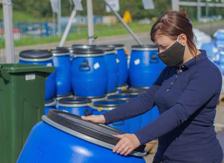 Woman wearing a virus protection mask holds a blue plastic barrel. In the background, you can see pallets with containers and an iron fence. Its a clear Sunny day outside. Stock fotó