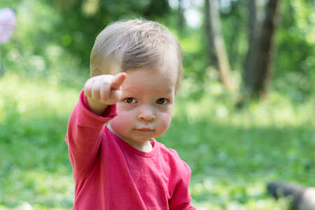 Child in a red shirt looks sternly at the camera and points an imperious finger. Stok Fotoğraf