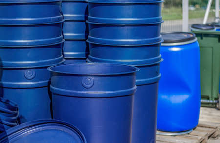 Huge blue buckets stand on wooden pallets. A blue barrel and a green tank can be seen in the background.