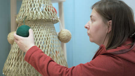 Woman in a red jacket decorates a homemade christmas tree made from laundry baskets and plastic clamps