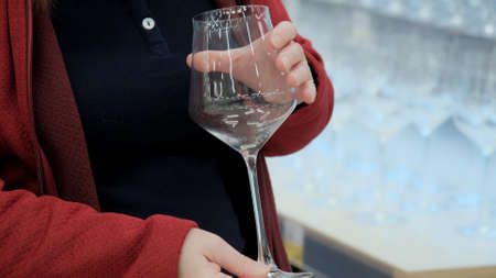 Girl in store chooses transparent wine glass with long stem. Camera shoots closeup of model hands. Rows of wine glasses are visible in the background Stock fotó