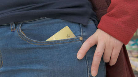 Bank card peeks out of the girl pocket. The contactless payment icon is visible on the map. Close up shot