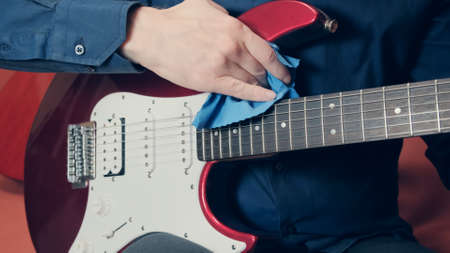 Men hands wipe a red electric guitar with a blue microfiber cloth. The hand slowly slides along deck of the instrument