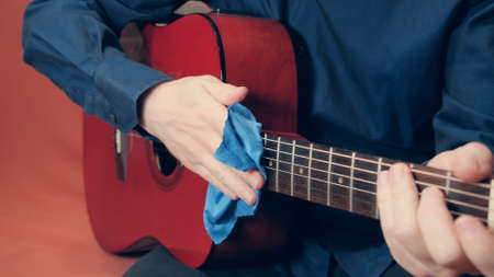 Men hands wipe a red acoustic guitar with a blue microfiber cloth. The hand slowly slides along the strings of the instrument Archivio Fotografico