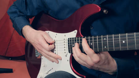 Caucasian man in a blue shirt plays an red electric guitar