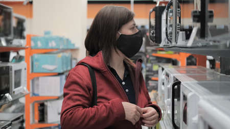 Caucasian women wearing antivirus medical mask and red jacket picks out microwave in electronics store. Concept of shopping during epidemic, pandemic