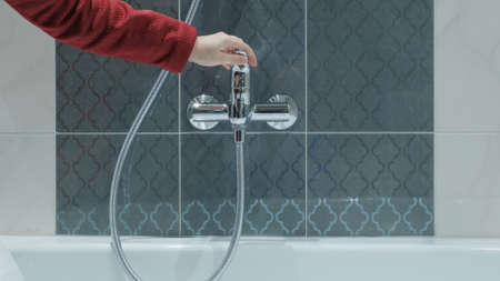 Woman in shop chooses water faucet. There are tiles all around. Concept of repair, construction and design. Screen from video footage Stock Photo