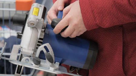 Woman in a shop chooses a portable, electric circular saw. Concept of womens independence, repair, construction and design. Screen from video footage