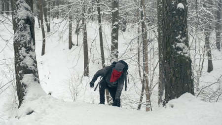 Climber with tourist backpack climbs snow covered mountain
