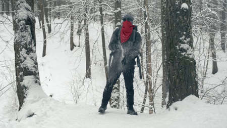 Climber in a red bandana and round, black glasses climbed a snow covered mountain and shakes off his gloves from the stuck snow