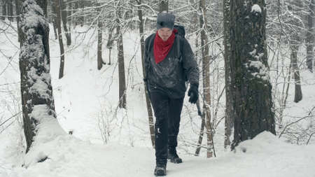 Climber with a red bandana and black sunglasses on his hat walks on a snow covered mountain Reklamní fotografie