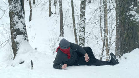 Male climber lies on the snow and touches his injured leg. Knife sticks out of the snow nearby. The concept of dangerous, extreme tourism
