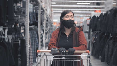 Caucasian woman wearing a mask and gloves against the virus drives a cart around the store and chooses outerwear for a man