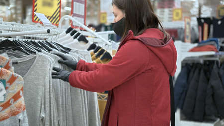 European girl wearing mask and gloves against virus chooses long sleeve shirts in a store. She goes through clothes on the rack looking at the sizes
