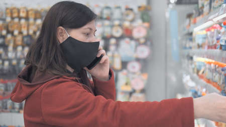 Caucasian woman wearing a mask against the virus stands in a grocery store. She on phone consulting with someone about buying products