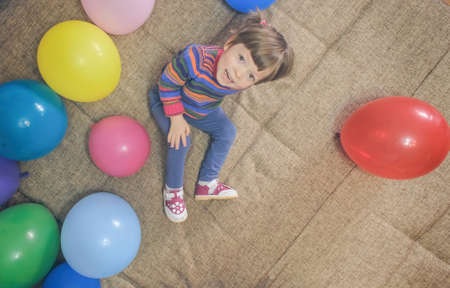 Little girl is playing with inflatable rubber balls while sitting on the sofa. She looks at the camera, smiles and makes a funny face. The camera shoots from above Banque d'images