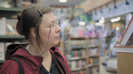 Serious caucasian woman with glasses on chain buys a book in bookstore. She carefully studies cover of a book on the shelf of a large store. Concept of reading, education and knowledge acquisition