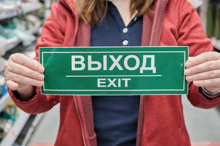 Woman holds a sign with the inscription exit in Russian and English. Concept of warning signs and mandatory compliance with occupational safety regulations. Hands close up shot