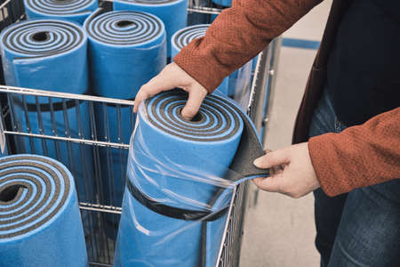 Woman in a shop chooses a blue travel, sports mat to buy. The concept of an active lifestyle and travels with a tent. Hands close up shot